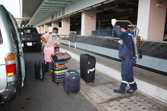 Medical workers spray with Chloramin B disinfectant for passenger's luggage