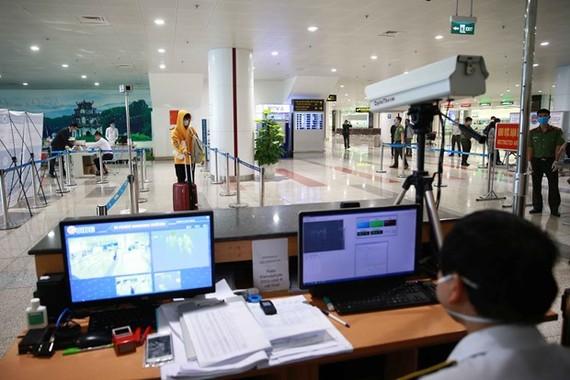 A staff member at Noi Bai International Airport in Hanoi checks passengers' body temperature via a thermal scanner (Photo: VNA)
