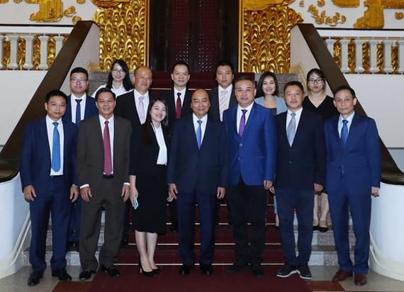Prime Minister Nguyen Xuan Phuc (front, center) and leaders of some Chinese businesses at their meeting on June 12 (Photo: VNA)