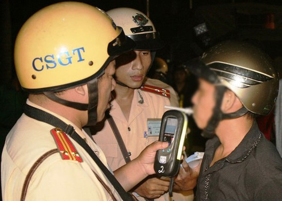 Police officers check blood alcohol level of a driver