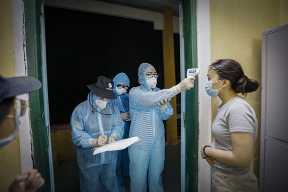 Health workers record health information of a woman at a quarantine site (Photo: VNA)