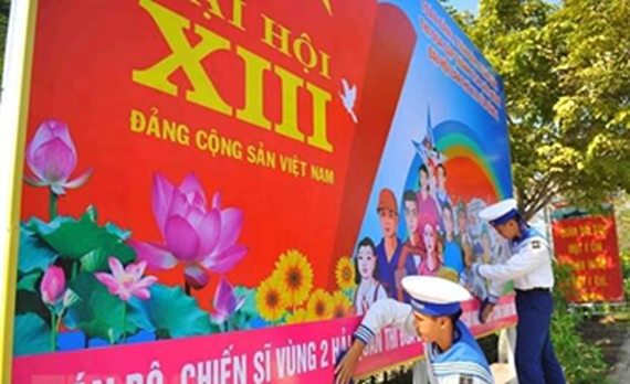 Naval soldiers hang on a poster to welcome the 13th National Party Congress (Photo: VNA)