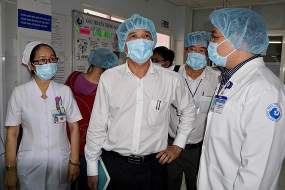 Bác sĩ Nguyễn Hữu Hưng, Phó Giám đốc Sở Y tế TPHCM (giữa) đi kiểm tra công khử khuẩn tại BV Từ Dũ. ẢNh: HOÀNG HÙNG