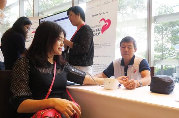 Người dân đo huyết áp tại hội nghị