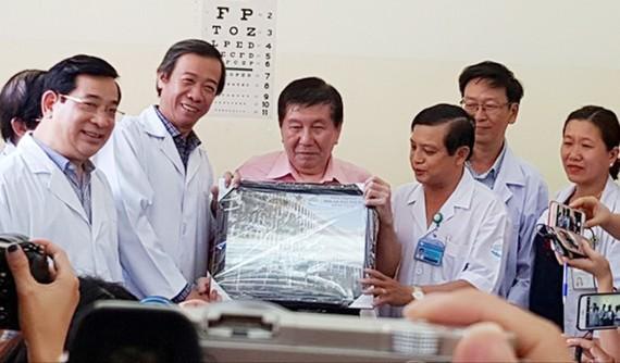 Bác sĩ Nguyễn Văn Vĩnh Châu, Giám đốc Bệnh viện Bệnh Nhiệt đới tặng bệnh nhân H. bức hình lưu niệm