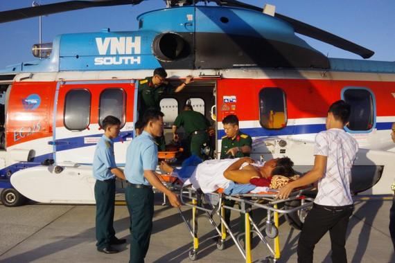 Các chiến sĩ, bác sĩ vận chuyển bệnh nhân từ trực thăng về bệnh viện Ảnh: TRẦN CHÍNH
