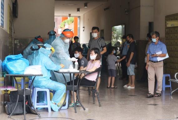 Lực lượng y tế đang lấy mẫu xét nghiệm cho cư dân Chung cư Thái An 2, quận 12