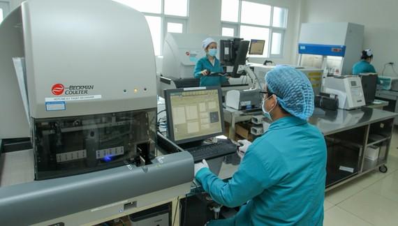 Nhân viên xét nghiệm tìm virus SARS-CoV-2 tại Bệnh viện 7A. Ảnh: HOÀNG HÙNG