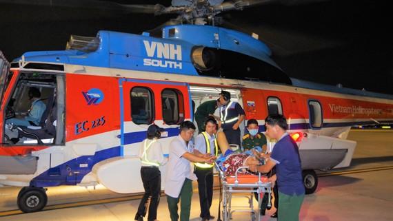 Lực lượng nhân viên y tế và nhân viên sân bay vận chuyển bệnh nhân từ trực thăng về bệnh viện