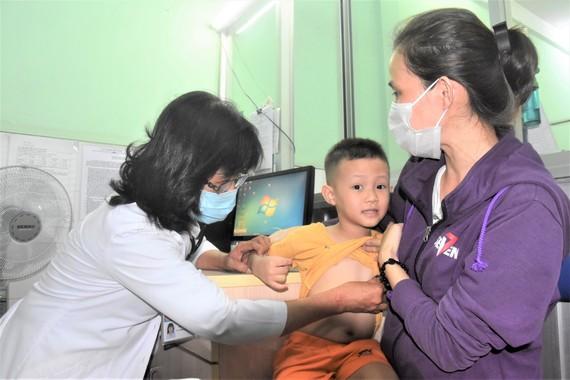 Bác sĩ Trạm y tế phường 2, quận Tân Bình đang khám cho bệnh nhi. Ảnh: QUANG HUY
