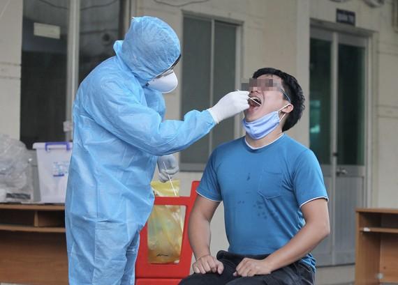 Nhân viên Trung tâm y tế quận 6 ̉lấy mẫu xét nghiệm cho người dân trên địa bàn. Ảnh: HOÀNG HÙNG