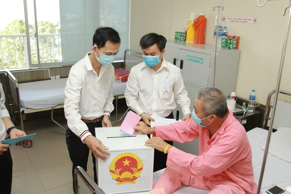 Thạc sĩ Lê Minh Hiển, Trưởng Phòng Công tác xã hội, Bệnh viện Chợ Rẫy cùng nhân viên UBND Phường 12, quận 5 mang thùng phiếu đến tận giường bệnh để bệnh nhân thực hiện quyền bầu cử