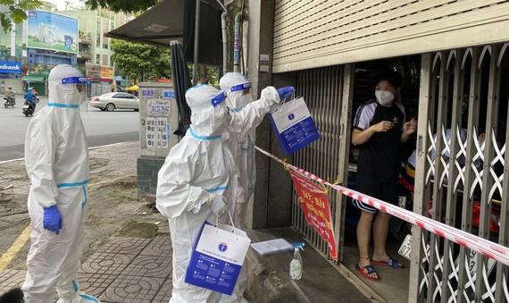 Nhân viên y tế phát thuốc tại nhà cho F0 ở quận 3 vào chiều 15-9. Ảnh: CAO THĂNG