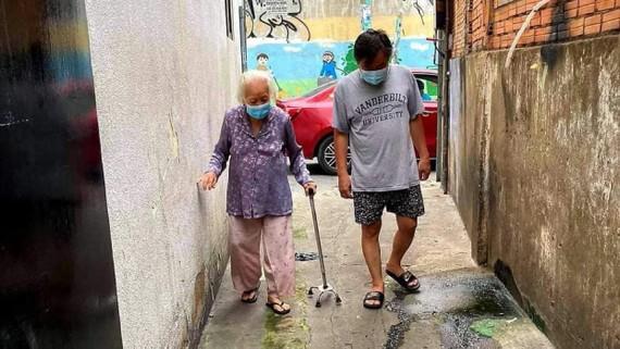 Cụ bà 92 tuổi mắc Covid-19 (bìa trái) tự đi bộ từ hẻm về nhà