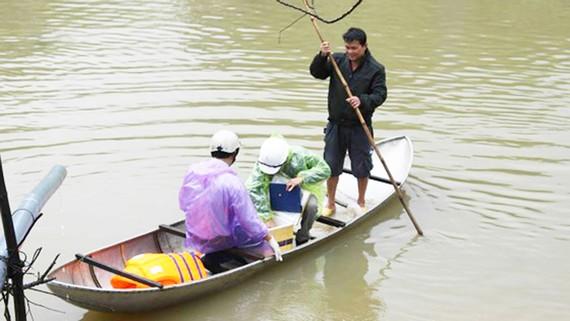 Tiến hành lấy mẫu nước tại khu vực xuất hiện cá và vịt chết.  Ảnh: NGUYỄN TRANG