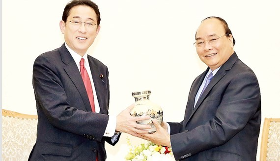 PM Nguyen Xuan Phuc ( R) presents a souvenir to Mr. Fumio Kishida