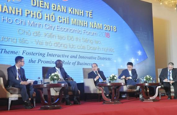 Bí thư Thành ủy TPHCM Nguyễn Thiện Nhân trao đổi cùng các diễn giả tại diễn đàn. Ảnh: CAO THĂNG