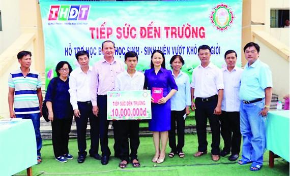 Ông Lưu Hoàng Tân - Chủ tịch, Giám đốc Công ty TNHH MTV Xổ số kiến thiết tỉnh Đồng Tháp (thứ 7 từ phải sang) trao học bổng cho em Vinh