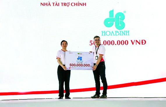 Ông Lê Viết Hải, CT. HĐQT kiêm TGĐ Hòa Bình (trái) trao tặng 500 triệu đồng cho chương trình