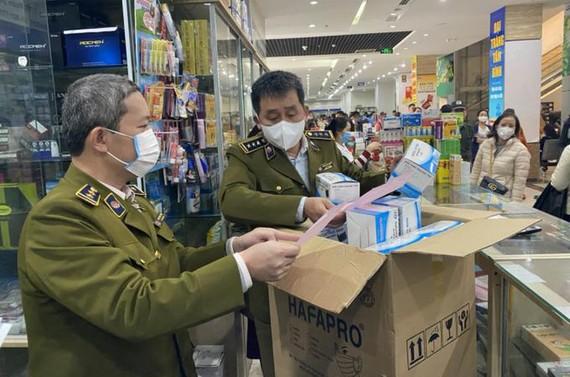 Đội Quản lý thị trường số 1 - Quản lý thị trường TP Hà Nội kiểm tra mặt hàng khẩu trang y tế tại một nhà thuốc ở Hà Nội. Ảnh: Tổng Cục quản lý thị trường.