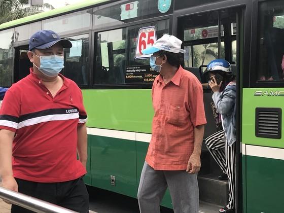 Hành khách đeo khẩu trang khi đi xe buýt. Ảnh: QUỐC HÙNG