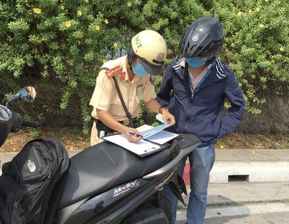 CSGT xử phạt người điều khiển phương tiện giao thông vi phạm khi qua hầm sông Sài Gòn. Ảnh: CAO THĂNG