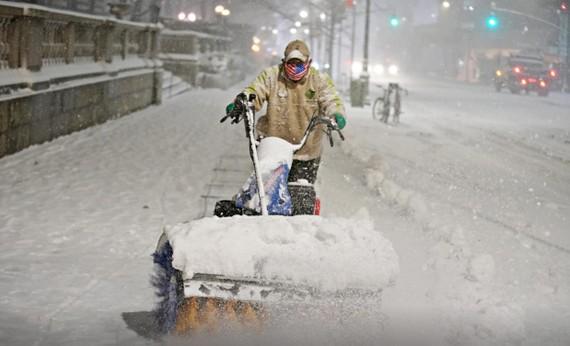 Người đàn ông dọn tuyết rơi dày ở Manhattan, TP New York, New York, Mỹ, ngày 16-12-2020. Ảnh: REUTERS