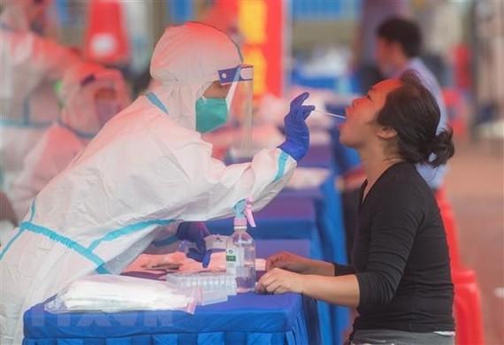 Nhân viên y tế xét nghiệm Covid-19 cho người dân tại Vũ Hán, tỉnh Hồ Bắc, Trung Quốc. Ảnh: THX