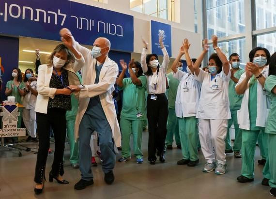 Nhân viên y tế vui mừng khi Israel bắt đầu đợt tiêm vaccine coronavirus, tại Trung tâm Y tế Tel Aviv Sourasky (Bệnh viện Ichilov) ở Tel Aviv, Israel, ngày 20-12-2020. Ảnh: REUTERS