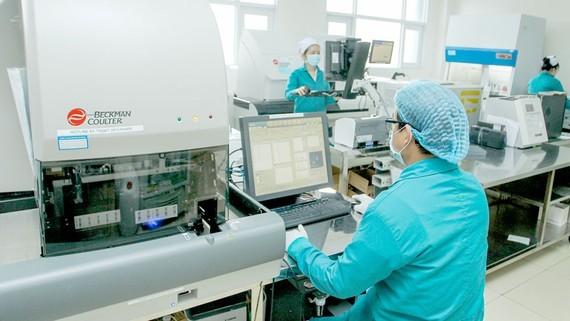 Nhân viên Bệnh viện Quân y 7A đang làm xét nghiệm tìm virus SARS-CoV-2. Ảnh minh họa: HOÀNG HÙNG