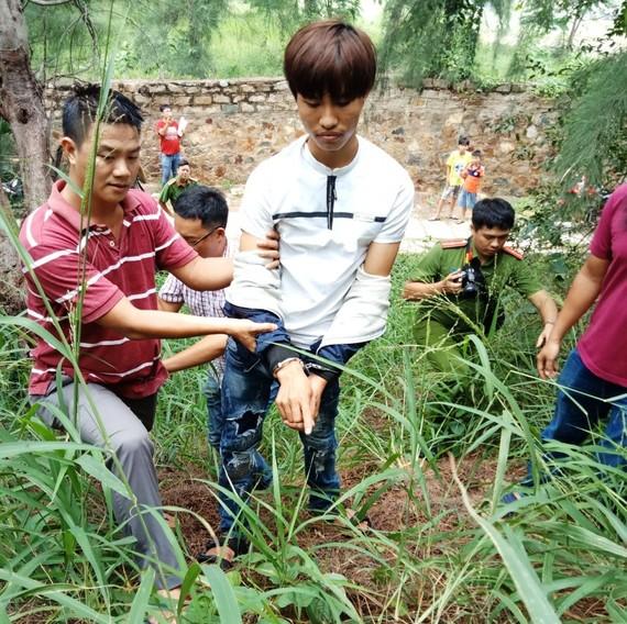 Đối tượng Cao Xuân Thắng (áo trắng) bị công an bắt giữ
