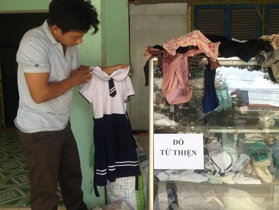 潘青峰整理慈善物品櫃裏的衣服。