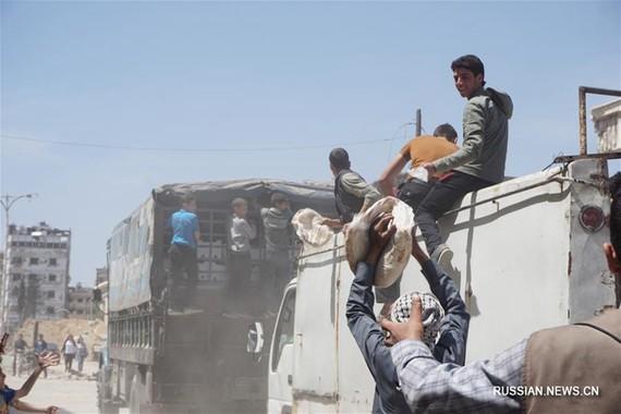 敘杜馬鎮街頭成廢墟, 民眾領救濟大餅。 (圖源:新華網)