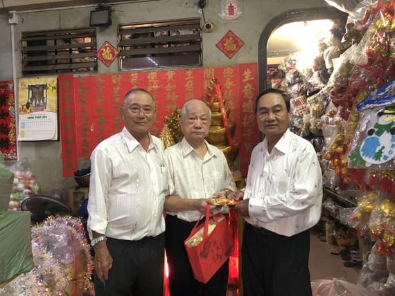 副會長黃炳友(左)、許永成(右)贈送禮物給楊光澤校友。