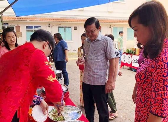 阮晉豐總編輯品嚐本報員工烹飪的華人美食。