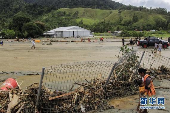 3月17日,在印度尼西亞巴布亞省森塔尼,一名婦女抱著孩子站在被洪水沖垮的圍欄旁。(圖源:新華社)