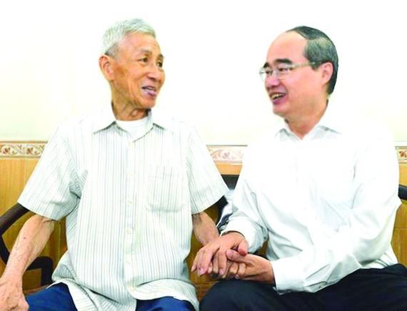 市委書記阮善仁親切問候華人革命老前輩何增同志。(圖源:越勇)