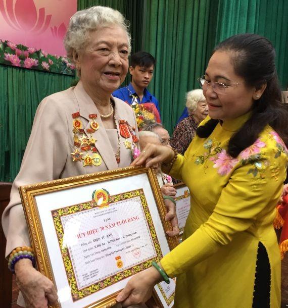 市人民議會主席阮氏麗(右)向葉秀英 大娘頒贈70黨齡紀念章。