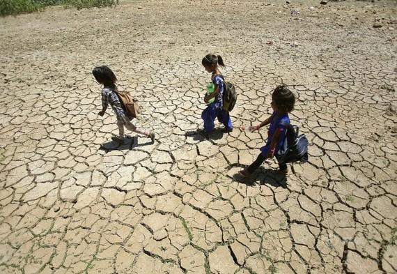當地時間2019年5月30日,印控克什米爾地區查謨,印度多地高溫,兒童行走經過乾涸的池塘,土地龜裂。(圖源:互聯網)