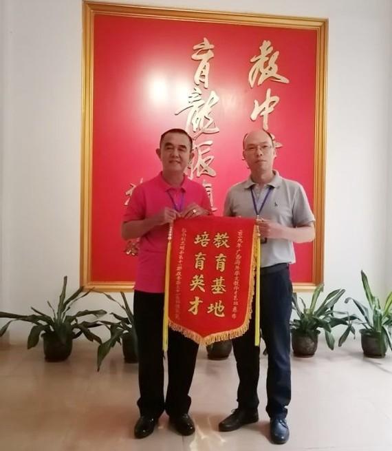 黃智球老師(左)代表本市華文老師團向組委會陳進超校長贈送紀念錦旗。