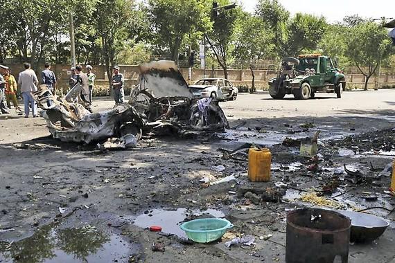 爆炸造成重大人員傷亡,校門附近商販的攤位嚴重受損,至少兩輛汽車被毀。(圖源:AP)