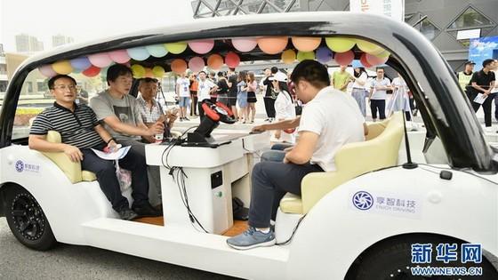 """8月28日,在""""5G自動駕駛科技示範體驗""""活動現場,重慶市民在一輛自動駕駛汽車挑戰賽的參賽車輛上進行5G自動駕駛真實城市道路試乘體驗。(圖源:新華社)"""