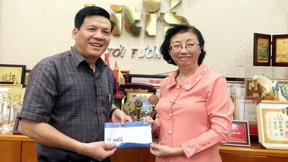 平仙公司副總經理陳芳珍(右)把贈報款項轉交給本報主編阮玉英(紅藍)。