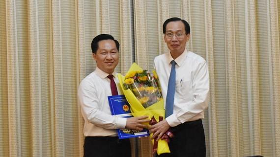 市人委會常務副主席黎清廉向黃松同志(左)頒授人事委任《決定》並送鮮花祝賀。(圖源:天理)
