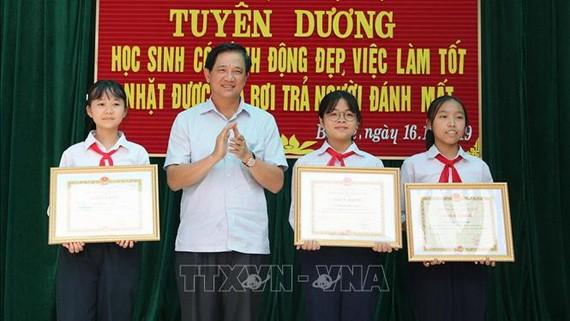 河內市教育與培訓廳副廳長范春進向三名拾遺不昧學生頒發獎狀。(圖源:越通社)