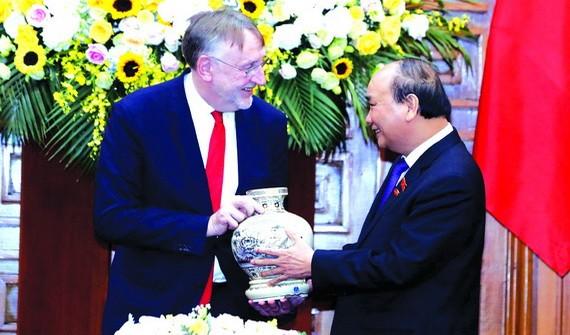 政府總理阮春福(右)向博納德主席贈送紀念品。(圖源:越通社)
