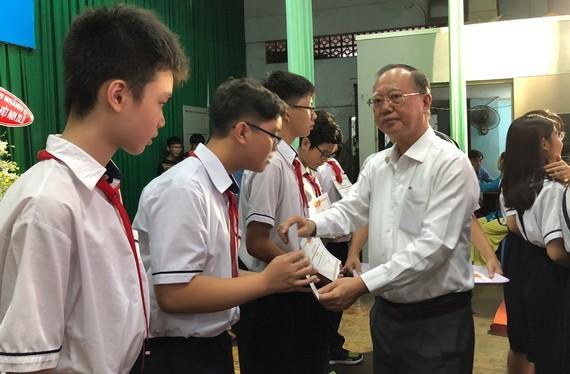穗城會館理事長盧耀南向郡級優秀生頒獎。