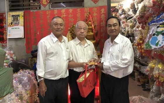 華人商販楊光澤(中)獲福中校友會贈送敬老禮物。