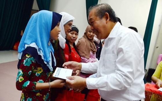 政府常務副總理張和平(右)向家境清貧的占婆族同胞贈送春節禮物。(圖源:B. Nghi)