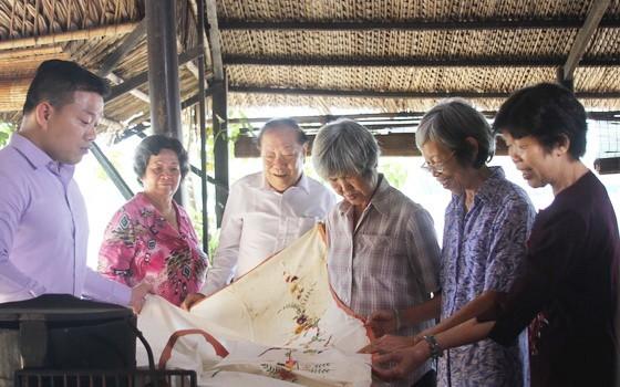 文物捐贈者在觀看劉麗英老師(右二)捐贈其母親昔日的嫁妝床簾。